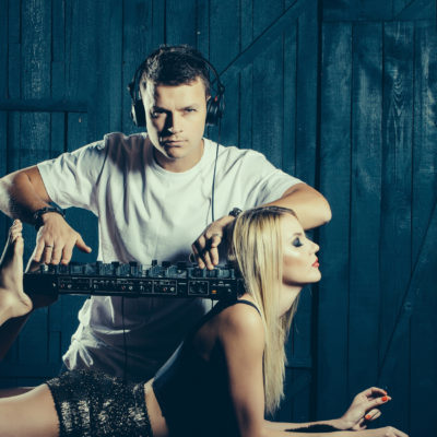 Young man musician in white shirt with headset playing dj mixer equipment standing on shoulders and legs of sexy glamour blonde girl on dark wooden background studio