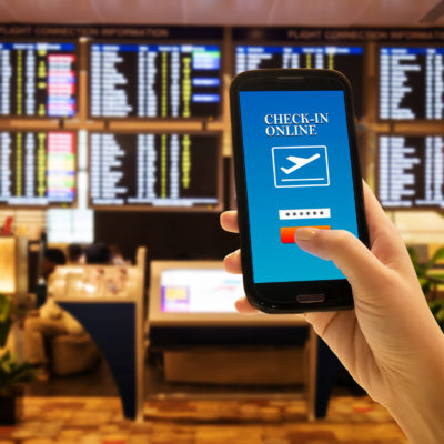 Traveler smartphone app concept. Close up of woman hand in international airport use mobile phone for check in online with flight information board background, checking her flight. Anonymous face