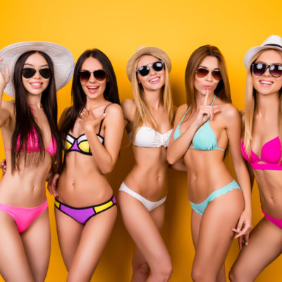 Joy, funky, chill, bachelor party mood. Five hot bridemaids are posing in trendy swimming suits and sunglasses, caps. They are protecting their healthy nice hair, skin and eyes from the strong sun