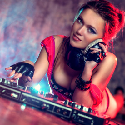 Young sexy woman dj playing music. Headphones and dj mixer on floor. Camera angle view.
