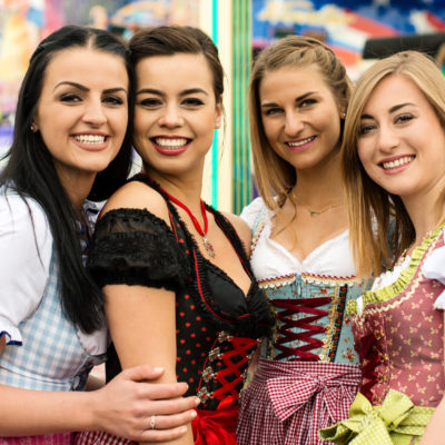 Joyful young and attractive women at German funfair Oktoberfest with traditional dirndl dresses and joyride in the background. Mixed nationalities, 2 girls rather typical German, one with Asian and Caucasian blend and one Russian girl, could also be Greek.
