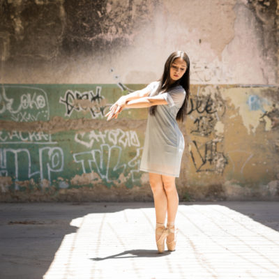 Attractive young female dancer performing outdoors in an abandoned building with graffiti walls