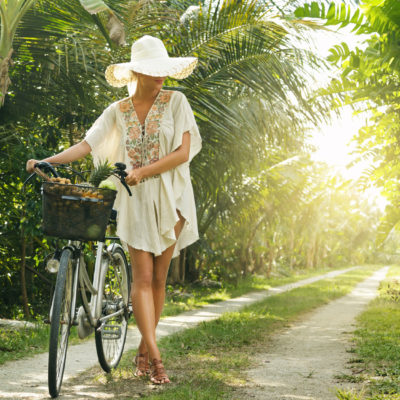 Beautiful woman wearing broad-brim hat in the tropical garden with a bicycle